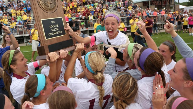 Members of the Ankeny girls soccer team lift senior Kelsey Laughman as they take the championship trophy after an overtime win over Pleasant Valley during the Iowa Class 2A state soccer championship match at Cownie Sports Complex in Des Moines on Saturday, June 13, 2015.