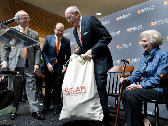 James Haslam hefts a bag containing 3,299 notes to him from students and faculty of the UT Haslam College of Business during a ceremony Nov. 14, 2014, at the University of Tennessee. Pictured from left are Dean Steve Mangum, Chancellor Jimmy Cheek, Haslam and his wife, Natalie Haslam.