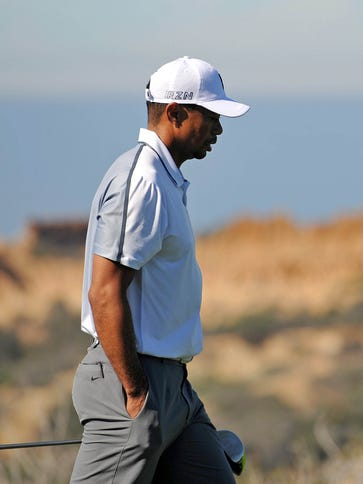Tiger Woods walks up the 13th during the first round
