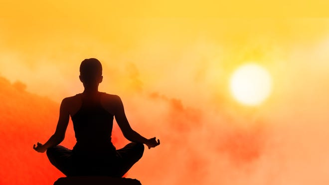 Woman meditating on high mountain in sunset background.