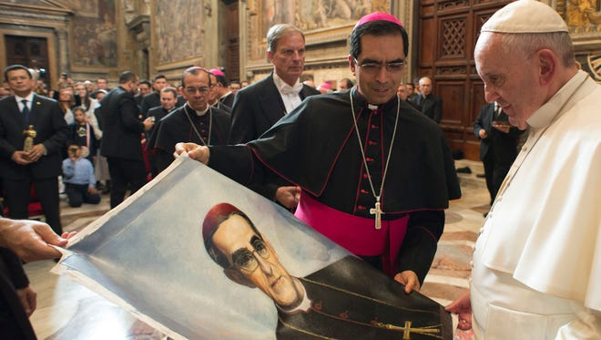 In this Oct. 30, 2015 file photo, Pope Francis is presented with an image of Roman Catholic Archbishop Oscar Romero during a private audience granted to participants to the pilgrimage from El Salvador at the Vatican. Pope Francis has cleared the way for slain Salvadoran Archbishop Oscar Romero to be made a saint, declaring that a churchman who stood up for the poorest of the poor in the face of right-wing oppression should be a model for Catholics today.