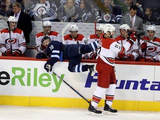 Carolina Hurricanes' Jordan Staal (11) almost hits Winnipeg Jets' Bryan Little (18) into the bench during the first period of an NHL hockey game, Saturday, Oct. 14, 2017 in Winnipeg, Manitoba. (Trevor Hagan/The Canadian Press via AP)
