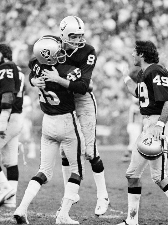 FILE - In this Dec. 28, 1975, file photo, Oakland Raiders kicker Ray Guy (8)  is hugged by teammate Neal Colzie in the closing seconds of the Raiders 31-28 win over the Cincinnati Bengals in a divisional playoff game in Oakland, Calif. Those anxious seconds for punt returners awaiting his booming kicks were nothing compared to the more than two decades Guy had to endure before finally getting the call that he was elected to the Pro Football Hall of Fame.  (AP Photo/File)