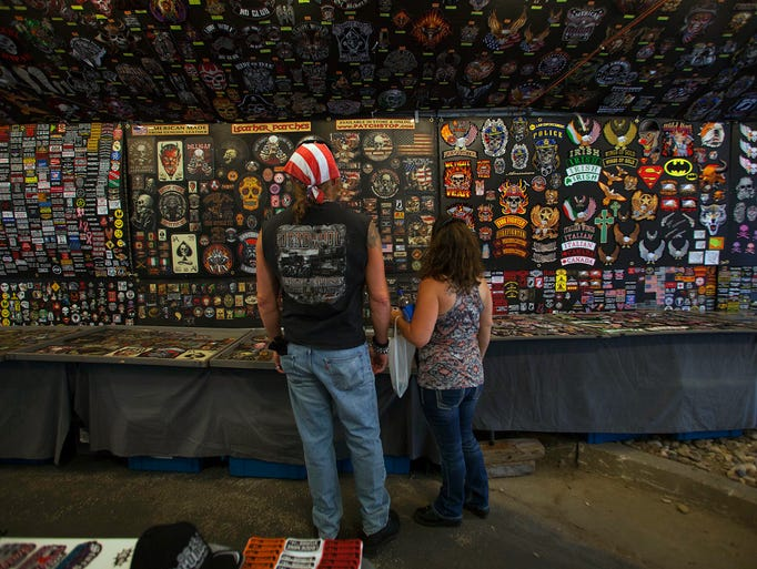 Eric Quinn, left, and his wife, Christine, of Golden, Colo., search for merchandise at the 74th Annual Sturgis Motorcycle Rally in Sturgis, S.D., on Friday, August 1, 2014.  Organizers expect attendance at this week's Sturgis Motorcycle Rally to top the estimated 466,000 who made the annual trek last year. (AP Photo/Toby Brusseau)