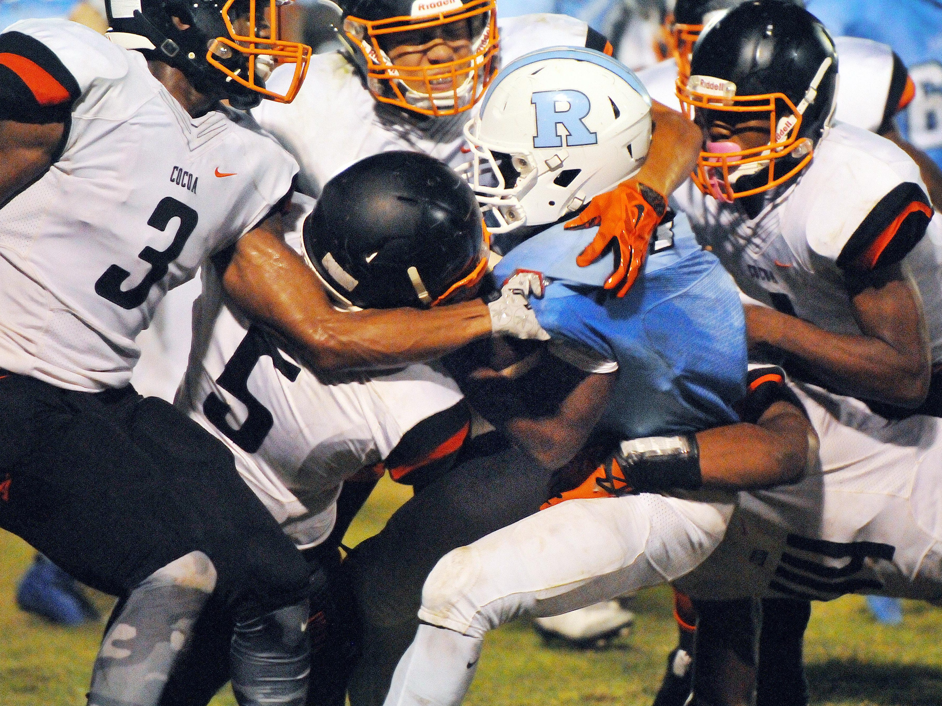 Cocoa High defenders swarm to the ball carried by Rockledge High's Jalen Mitchell (7) during Friday night's BBQ Bowl game held at McLarty Stadium.
