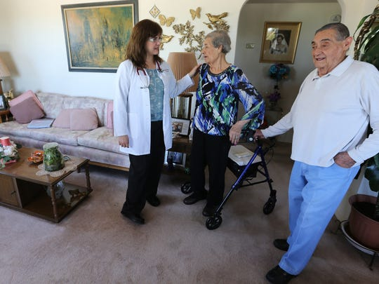 Dr. Martha Manquero-Butler, left, visits with Carlota and Jose Navarro Friday at their home.