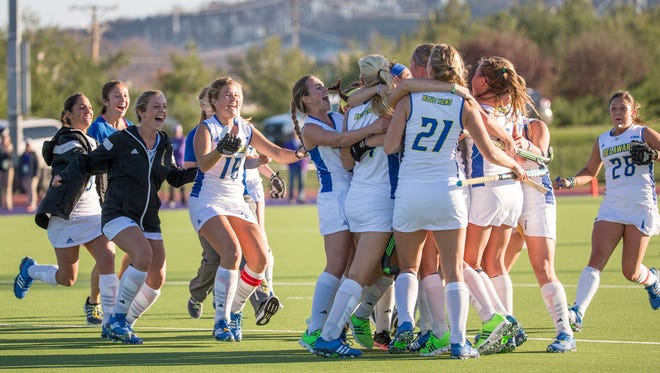 Delaware field hockey players mob Lisa Giezaman after her overtime goal won the CAA title.