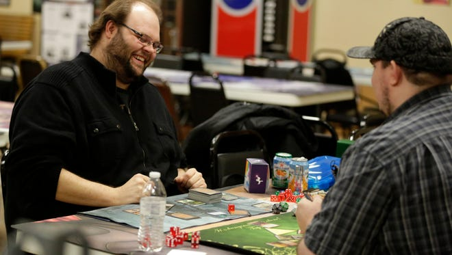 Brandon Hopfensperger (left) enjoys a laugh with Andy Brietzke as they play Magic: The Gathering earlier this week at Chimera Hobby Shop in Appleton.
