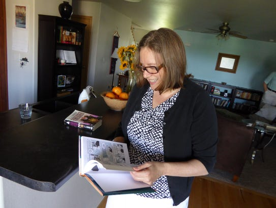 "Joan Benson reads through her copy of ""Fun Home,"" by"