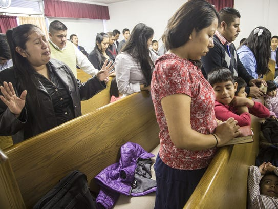 Family from Guatemala prays at one of the churches