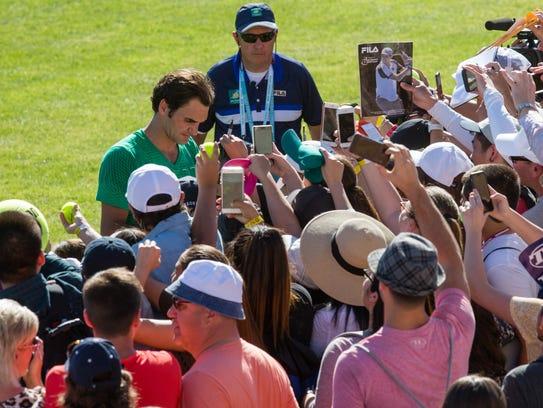 Roger Federer signs autographs for fans at the BNP