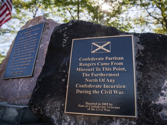 A confederate battle flag is displayed on a monument