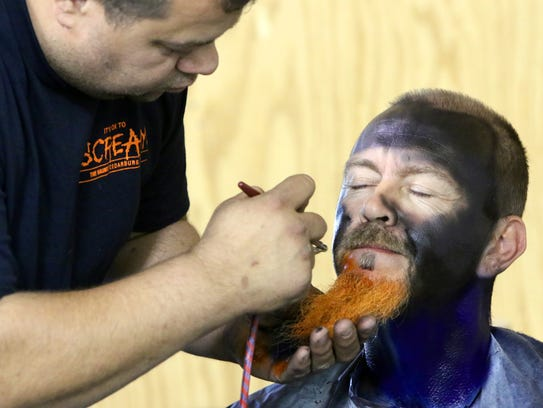 Dan Cehanovich of Port Washington uses an airbrush to apply makeup to Lenny Ainsworth of Germantown as one of the characters at The Haunt.