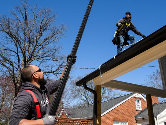 Jason Hernandez of Summit Solar hands Nick Messer a metal beam as they install solar panels on the roof of a home on Thursday, March 15, 2018.