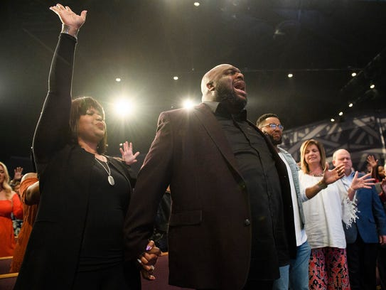 Pastor John Gray sings during a farewell service in honor of Ron and Hope Carpenter, the founders of Redemption Church, which is now called Relentless and led by Gray.