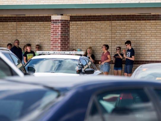 People wait at Santa Fe Junior High School to be taken