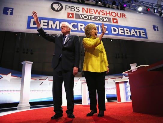Bernie Sanders and Hillary Clinton walk out on stage
