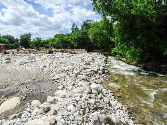 In this Monday, July 3, 2017, photo, the Neshobe River runs along a washed away portion of Newton Road in Brandon, Vt., after heavy rains on July 1. According Daryl Burlett, Director of Brandon Public Works, rocks clogged the river up stream, causing it to divert its path across Newton Road.