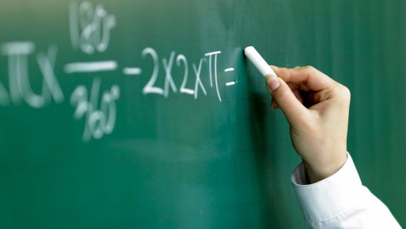 Teacher writing on chalkboard.