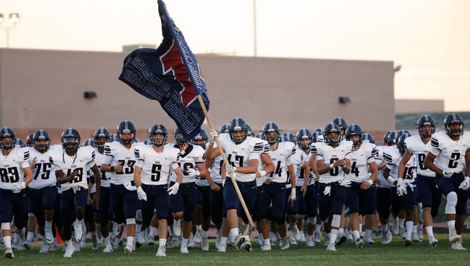 The Gilbert Perry football team takes the field before a game at Phoenix Desert Vista on August 18, 2017.