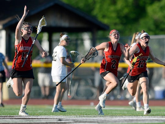 Penfield's Shannon Burdick, left, Lucy Rugaber and Madigan Lublin celebrate their win in the Section V Class A championship game at East Rochester High School, Tuesday, May 29, 2018. No. 4 seed Penfield won the Class A title with an 8-6 win over No. 2 seed Rush-Henrietta.