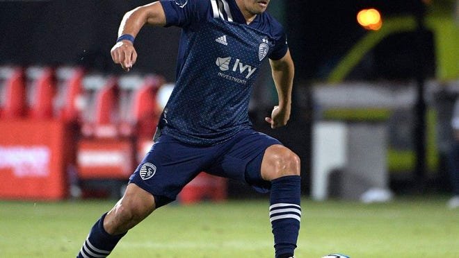 In this July 12, 2020, file photo, Sporting Kansas City midfielder Roger Espinoza pushes the ball on the pitch during the second half of an MLS soccer match against Minnesota United in Kissimmee, Fla.