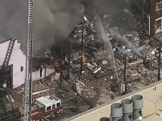 In this image taken from video, firefighters and emergency