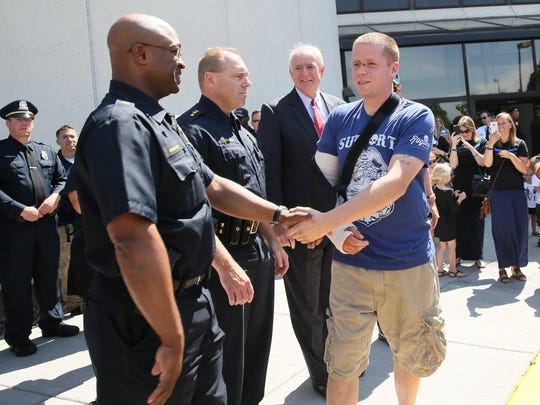 Officer Brandon Baranowski is greeted by command staff from MPD and Milwaukee Mayor Tom Barrett as he leaves the hospital.