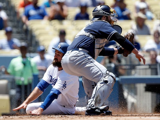 Los Angeles Dodgers' Scott Van Slyke, left, slides in to score as he beats the throw to San Diego Padres catcher Derek Norris, right, during the second inning of a baseball game in Los Angeles, Sunday, July 10, 2016. (AP Photo/Alex Gallardo)