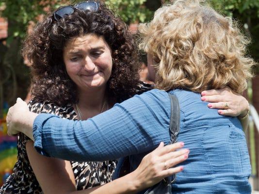 Teacher Fran Reinhard, a 27-year employee of the district, hugs Dinah Clark, a secretary at Grace E. Loucks Elementary School in West York from 1989-2010.