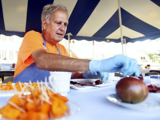 Tom Newcomer serves tomatoes for the Franklin County Master Gardeners tomato tasting and competition in Chambersburg on Saturday. This year, 35 different kinds of tomatoes were available for tasting by attendees.