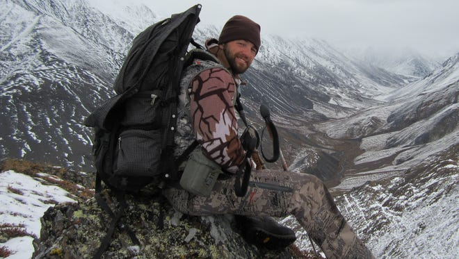 Adventurer and guide Billy Molls sits high atop Alaska's Brooks Range mountains in pursuit of Dall sheep.