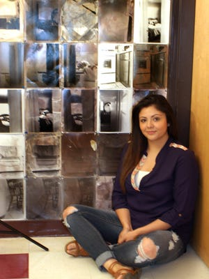 Monica Pacheco in front of her photo installation