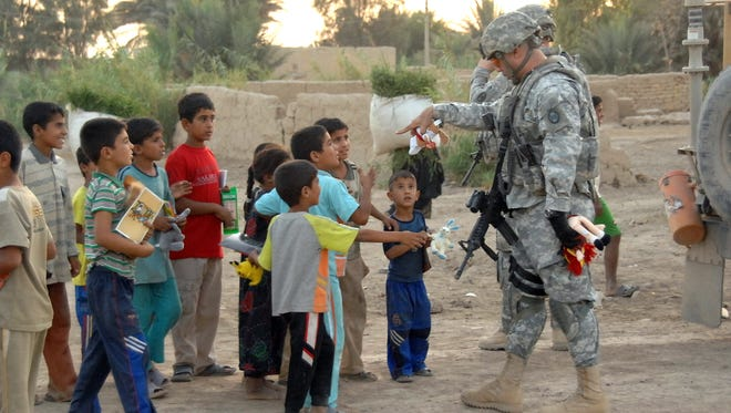 U.S. Soldiers from the 30th Heavy Brigade Combat Team, 1st Cavalry Division, pass out toys to local children during a Human Terrain Team site survey mission, in Kilabeen, Iraq, Sept. 15. 2009.