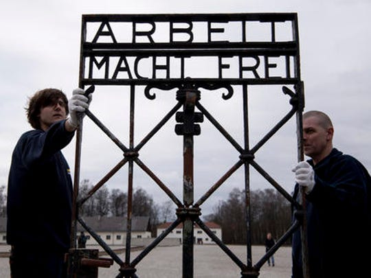 "Employees of a transport company carry the gate with the writing ""Arbeit macht frei"" (Work Sets you Free) at the memorial of the former  Nazi concentration camp in Dachau, Germany, Wednesday, Feb. 22, 2017.  The gate  was stolen in 2014 and reappeared in November 2016 near the city of Bergen in Norway."