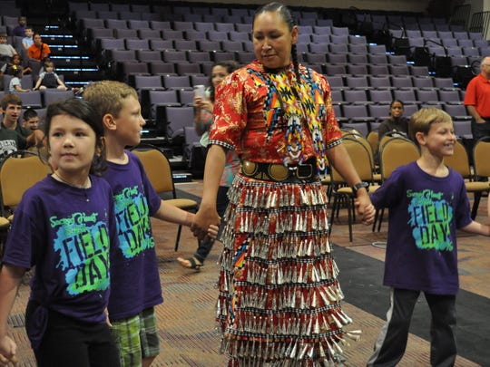 Around 400 students visited the Paragon Casino Resort in Marksville on Friday for a sample of the annual Tunica-Biloxi Pow Wow. Rowena Roberts (middle) of Ada Oklahoma, dances with Avoyelles Parish elementary students during the field trip opportunity offered by the Pow Wow committee.