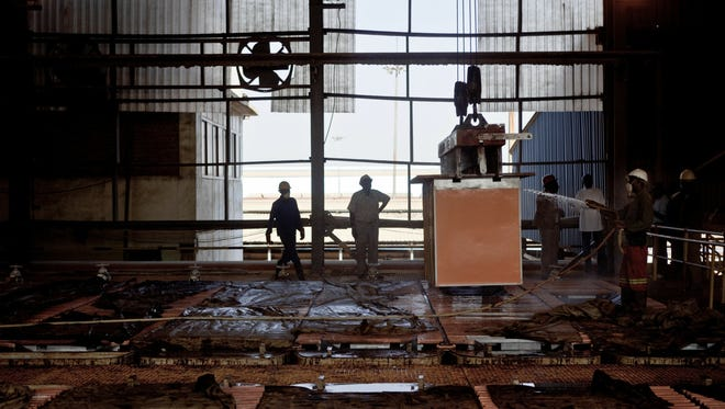 Workers clean copper plates produced at the Chemical of Africa (CHEMAF) factory in Lubumbashi on July 8, 2010.