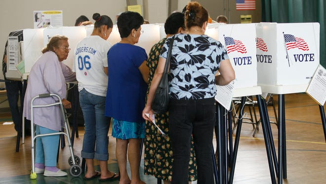In this June 6, 2006, file photo, people cast their ballots in the California primary election in Los Angeles. With fewer than a fourth of voters showing up for recent local elections, the city'?s Ethics Commission voted Thursday to recommend that the City Council consider a cash-prize drawing as an incentive to vote.