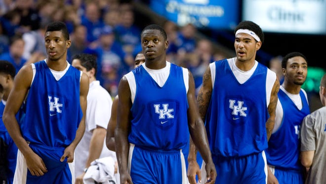 Kentucky Wildcats forward Marcus Lee (far left) and forward Julius Randle (middle) and  forward Willie Cauley-Stein (right) walk out on the court after a time out during the Kentucky Blue-White Scrimmage at Rupp Arena.