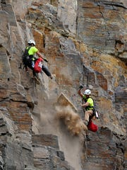 Two scalers with Triptych construction work together to remove a rock from the cliff face over I-15 near Sieben Ranch on Wednesday morning.