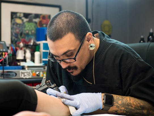 Gypsy Skull Tattoo owner Brian Fuentes works on a on
