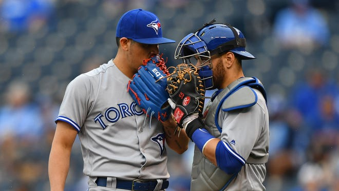 Toronto Blue Jays pitcher Roberto Osuna (left) talks with catcher Russell Martin (right) against the Kansas City Royals during the ninth inning at Kauffman Stadium.