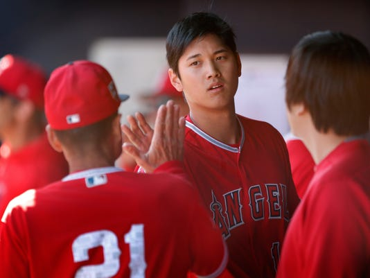 Los Angeles Angels Shohei Ohtani, center, talks with third base coach Dino Ebel, left, during the first inning of a spring training baseball game against the San Diego Padres, Monday, Feb. 26, 2018, in Peoria, Ariz. (AP Photo/Charlie Neibergall)