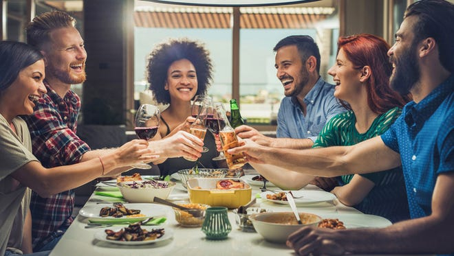 People having fun at dinner party and toasting with alcohol.
