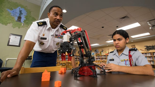Golden apple winner Jesse Bryson, a JROTC instructor at Fort Myers High School, works with student Jemineth Reyes, 15, a cadet captain, during a mechanical crane exercise Monday, 3/27/17. Bryson and a handful of cadets were visiting elemenatry students at James Stephens Academy, as part of a mentoring program with the academy.