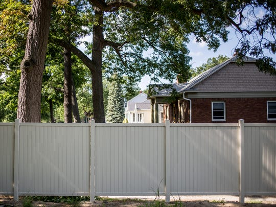 A fence is seen erected along a property line Wednesday, July 20, 2016 at Palmer Park in Port Huron. The city installed the fence last year after two residents who live adjacent to the park complained about noise.