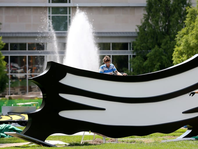 "Jon Brewer places an eye bolt in a piece before it is set into place during the installation of ""Five Brushstrokes"" by Roy Lichtenstein, on Wednesday, July 30, 2014, at the Indianapolis Museum of Art. The IMA will hold a block party on Aug. 29 to unveil the works to the public."