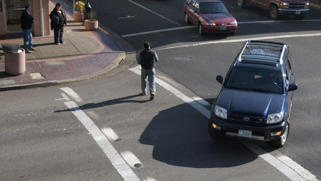 In this file photo, pedestrians, cross walk and cars at the intersection of Liberty and Ferry streets NE on Thursday Feb. 10, 2005. This intersection was not the intersection of the pedestrian safety campaign.