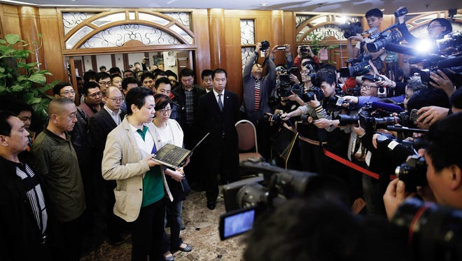 Representatives of relatives of passengers on Malaysia Airlines Flight 370 make a statement  at the Lido Hotel on Monday in Beijing.