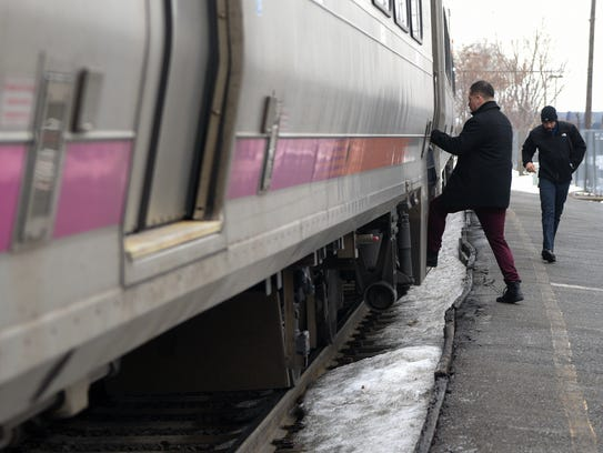 Passengers board an NJ Transit train at the Clifton